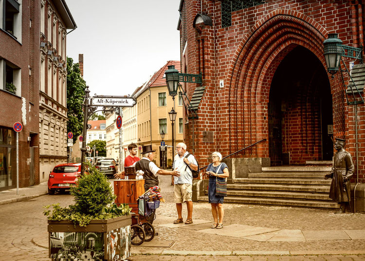 Adult Architecture Bicycle Bonding Building Exterior Built Structure Casual Clothing City Life Day Full Length Hauptmann Von Köpenick Land Vehicle Lifestyles Men Mode Of Transport Organ Grinder Outdoors Real People Street Togetherness Transportation Women Young Adult
