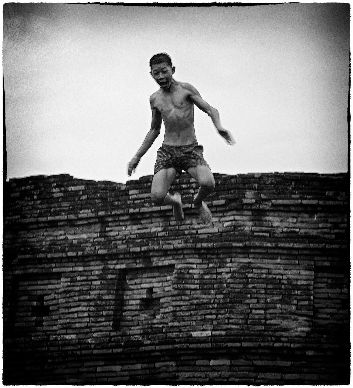 full length, shirtless, human representation, low angle view, day, outdoors, built structure, front view, childhood, building exterior, architecture, jumping, statue, sculpture, real people, one person, sky, people