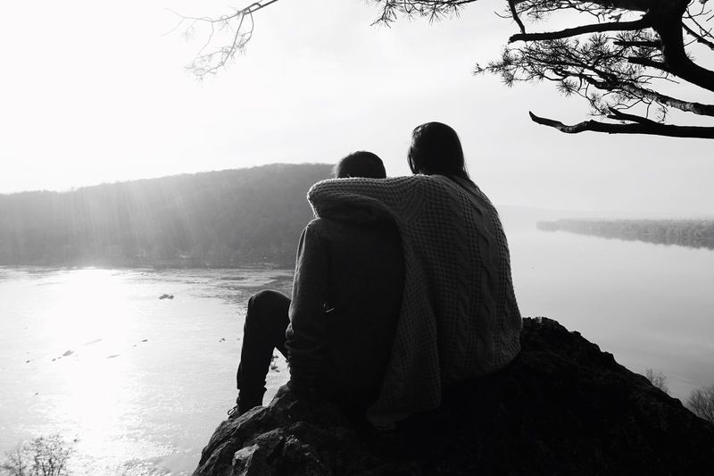 Rear View Togetherness Two People Lake Real People Water Sitting Men Nature Tranquility Leisure Activity Day Beauty In Nature Love Tranquil Scene Tree Outdoors Scenics Women Lifestyles Go Higher