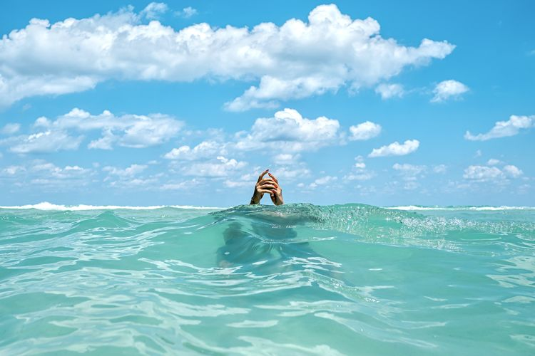 Scenic view, swimmer in the ocean, hands in the air