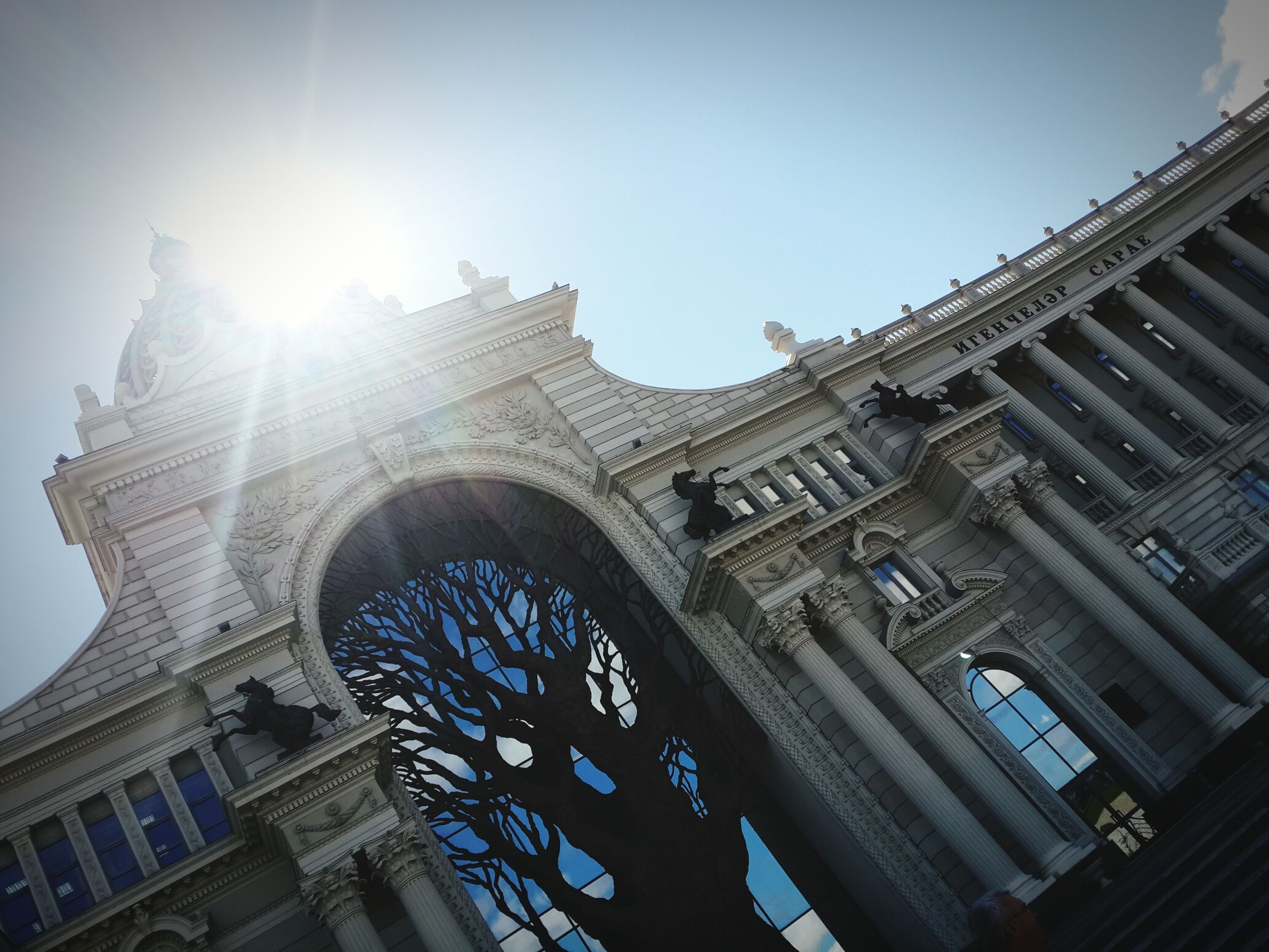 architecture, built structure, building exterior, low angle view, sun, sunbeam, sunlight, clear sky, city, lens flare, sky, tower, travel destinations, famous place, tall - high, sunny, building, day, capital cities, outdoors