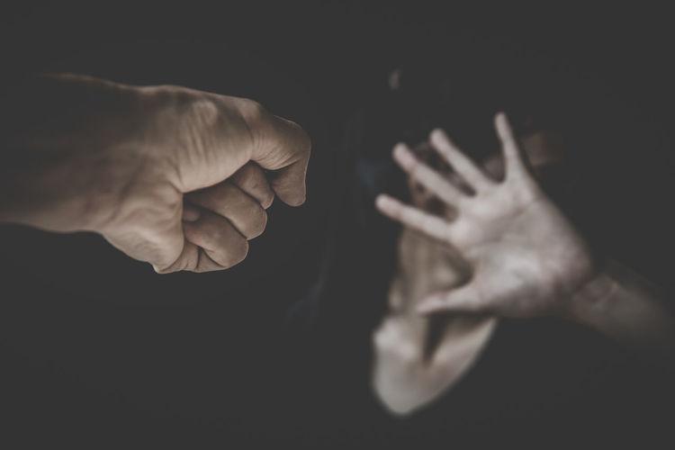 Close-up of hands holding leaf against black background
