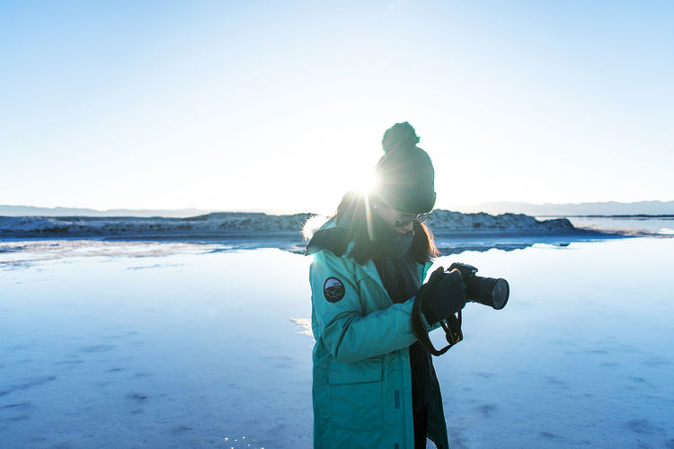 Man photographing woman holding camera while standing by sea against sky