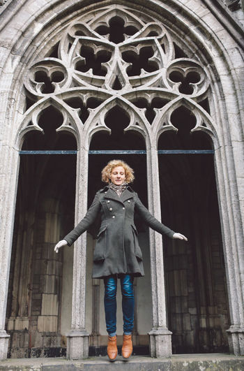 Low angle view of woman standing under rose window