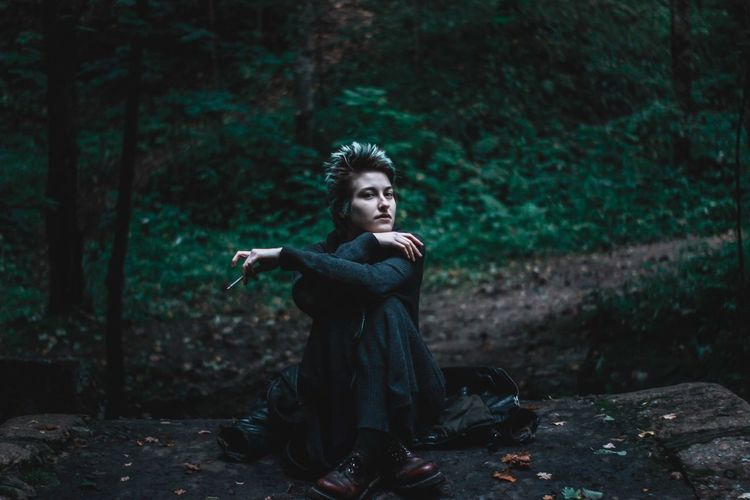 Portrait of young woman sitting in forest