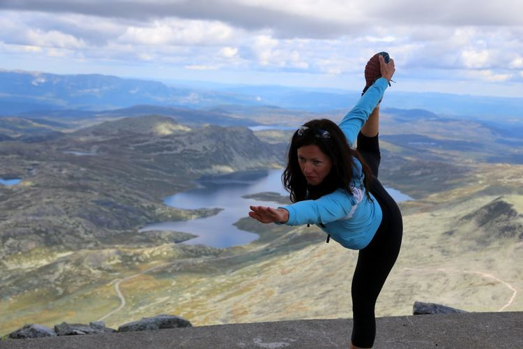 Woman doing standing bow pulling yoga pose and meditation on top of Gaustatoppen, Telemark, Norway. Adult Day Hatha Yoga Individuality Landscape Leisure Activity Mountain Nature One Person One Woman Only Only Women Outdoors People Photo Messaging Photography Themes Portrait Real People Scenics Standing Bow Stehender Bogen Yoga Yoga Outdoor Yoga Pose Yogagirl Young Adult