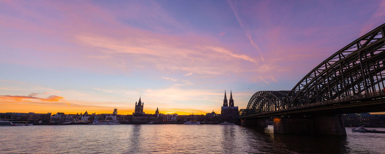 Cologne skyline with Cologne Cathedral and Hohenzollern bridge at night Cologne Cologne Cathedral Cathedral Sky Architecture Built Structure Bridge Water Cloud - Sky Bridge - Man Made Structure Connection Sunset River Building Exterior Transportation Waterfront Nature City Travel Destinations No People Travel Outdoors Cityscape