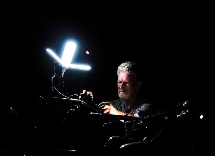 Senior man repairing motorcycle in darkroom
