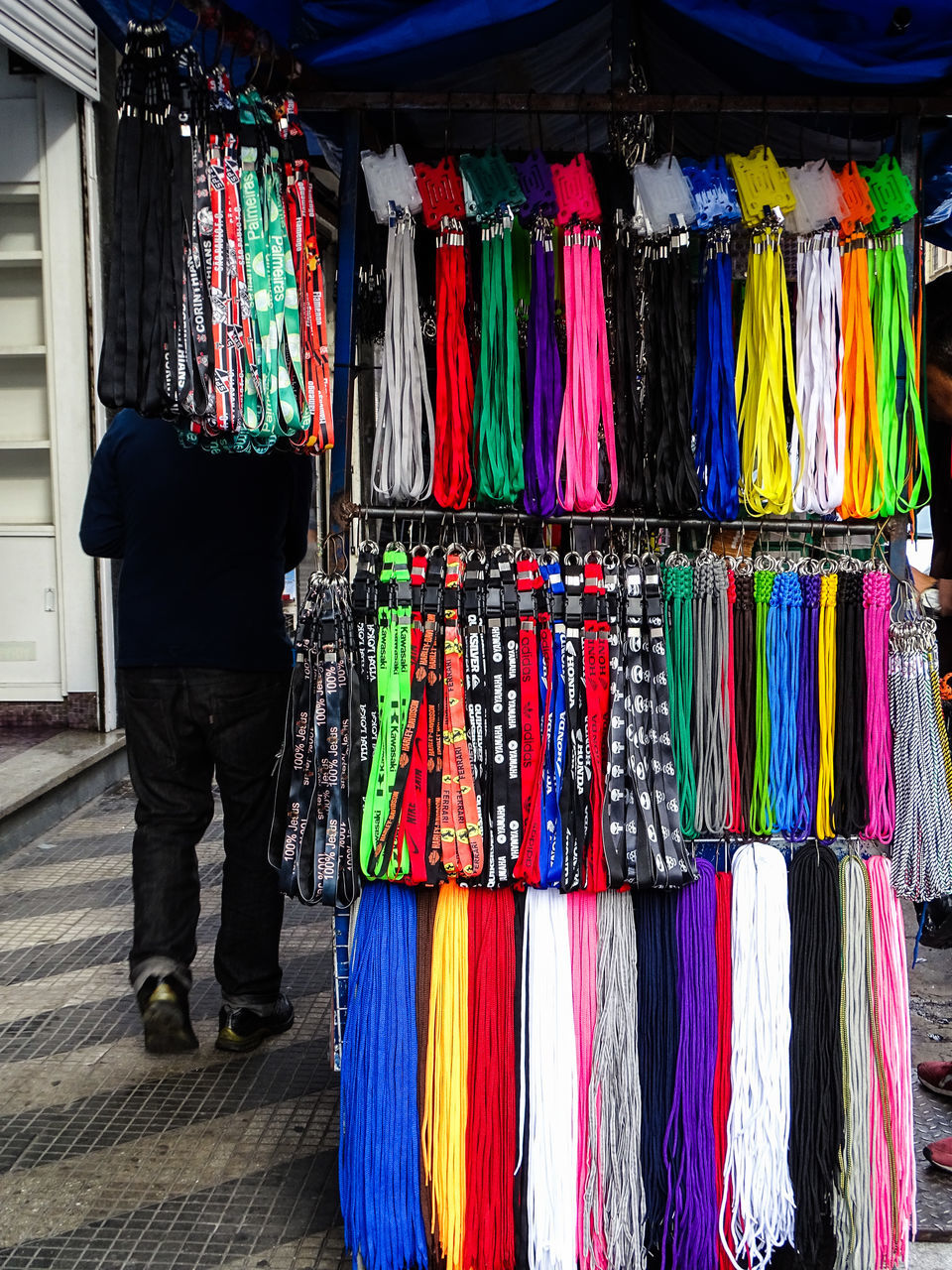 multi colored, for sale, large group of objects, retail, clothing, stack, variation, hanging, casual clothing, real people, one person, cloth, men, indoors, day, people