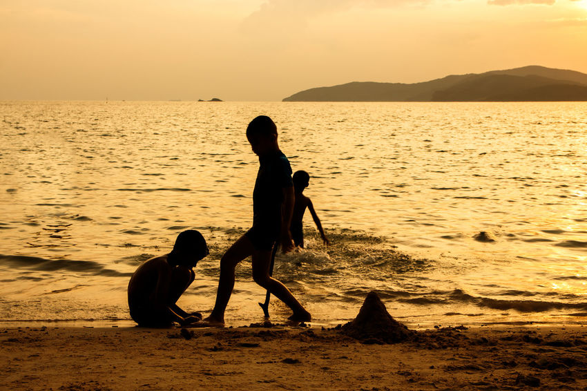 silhouette of people at the beach,The beauty of natural light at sunset. Water Real People Sky Sea Two People Beauty In Nature Sunset Beach Togetherness Lifestyles Women Scenics - Nature Land Family Nature Leisure Activity Silhouette Child Adult Positive Emotion Outdoors Silhouette Happiness Happy People Holiday Relaxing Children Man Romantic Orange Clouds And Sky Love Family Summer Sunrise Boy Freshair Freedom Fun