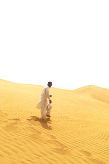 Full Length Of Man Walking On Sand Against Clear Sky
