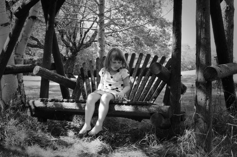 Full length of cute girl swinging in park