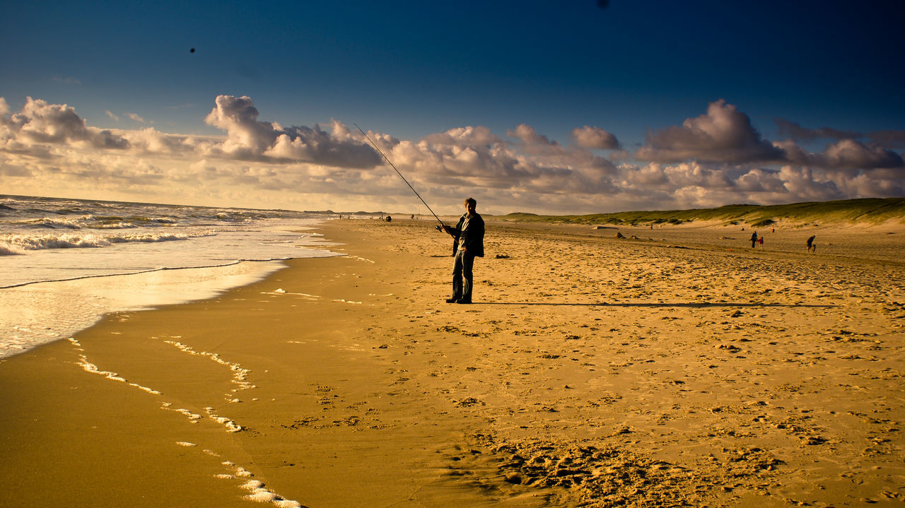 Full Length Of Man Fishing While Standing At Beach