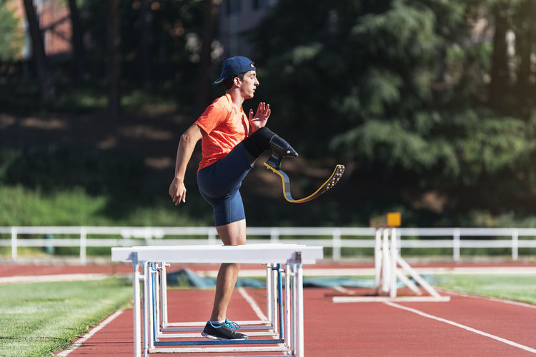 Side view of young athlete stretching prosthetic leg by railings at running track