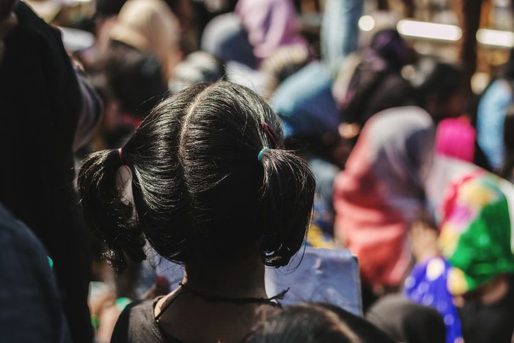 Rear view of girl standing by crowd during protest