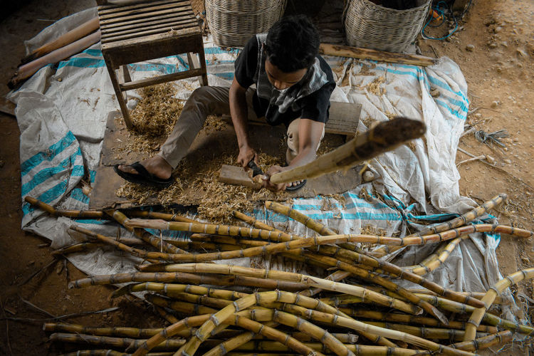 High angle view of man cutting sugarcane