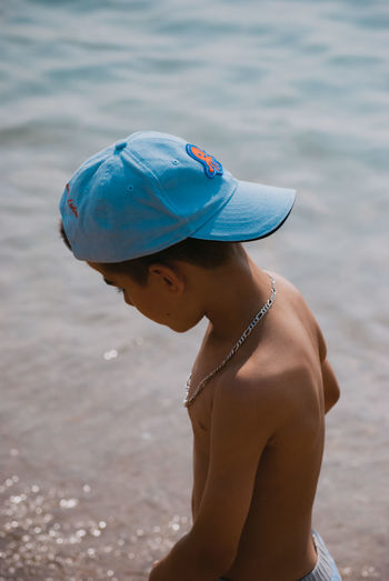Side view of shirtless boy standing in sea during summer