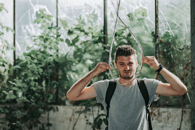 Portrait of young man holding rope standing against plants
