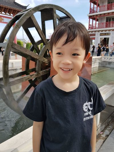 Thoughtful Boy Smiling While Standing Against Watermill In Pond