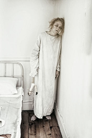 Spooky patient standing against wall at hospital