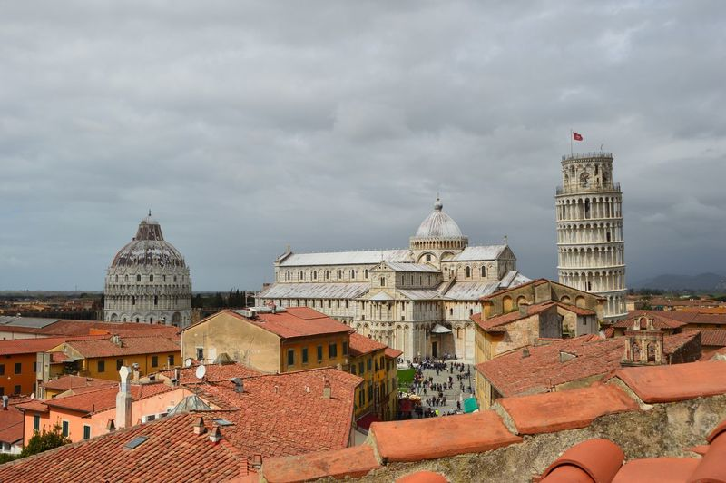 Historic leaning tower of pisa in city against cloudy sky