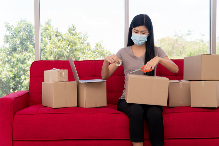Young woman with mask packaging while sitting on sofa