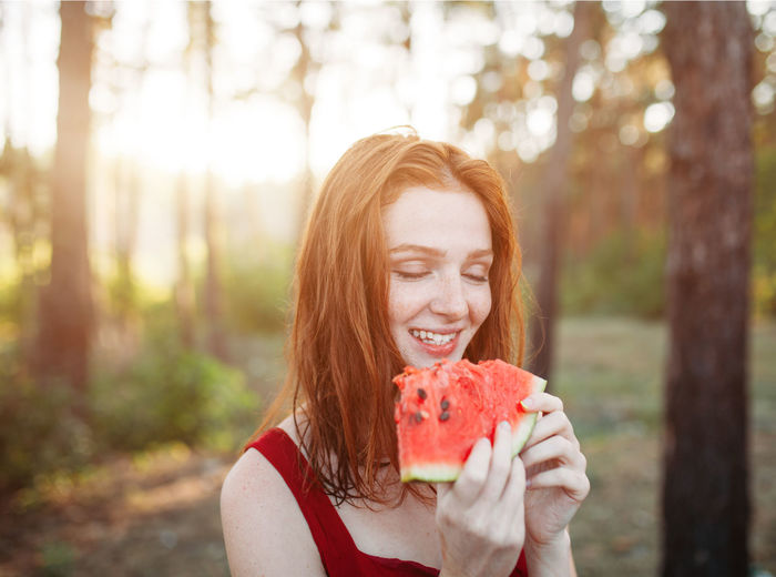 Close-up of smiling woman with eyes closed eating melon in forest