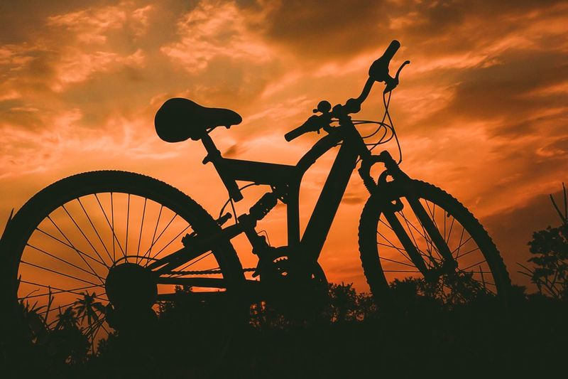Sunset Transportation Sky Silhouette Bicycle Cloud - Sky Wheel Mode Of Transportation Nature Orange Color Land Vehicle Outdoors Low Angle View No People Outline Plant Back Lit Dusk Dramatic Sky Travel