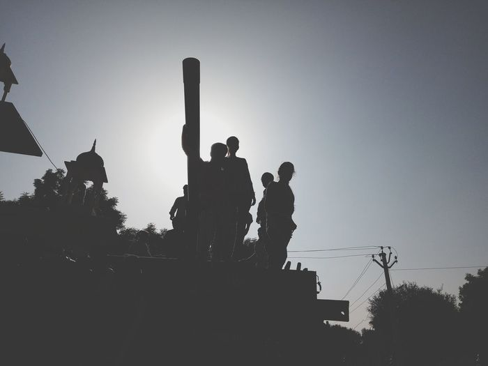 Low angle view of silhouette people against clear sky