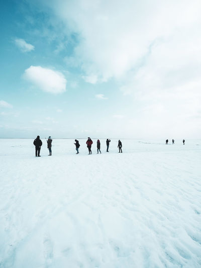 Tiny people at snow in sunny day