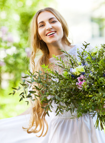 Portrait of smiling young woman against white flowering plants
