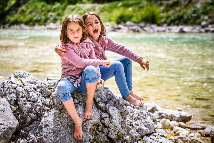 Portrait of sisters sitting on rock against lake