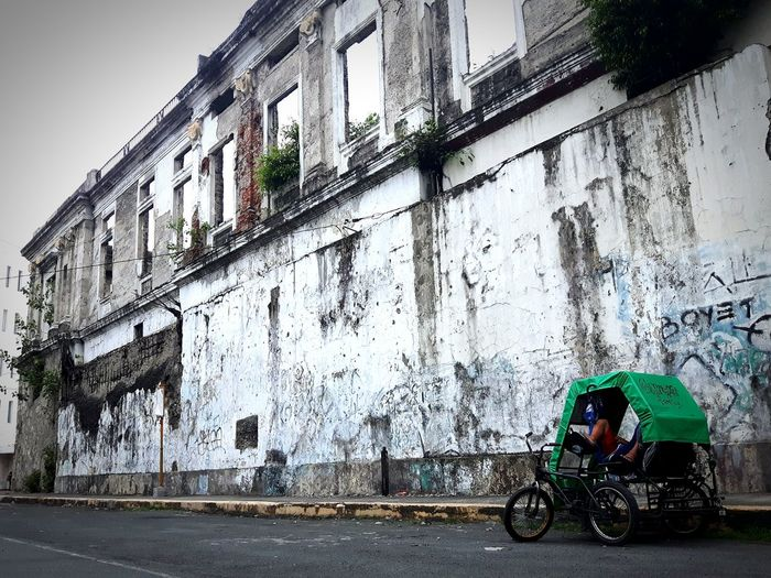 Rickshaw on street by building