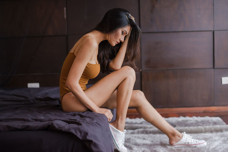 Side View Of Young Woman Wearing Swimsuit And Canvas Shoes In Bedroom At Home