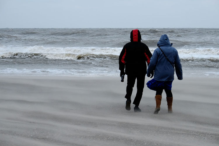 Man and woman on stormy beach looking at the sea Beach Beauty In Nature Couple - Relationship Full Length Horizon Over Water Land Leisure Activity Motion Nature Outdoors People Real People Rear View Sea Sky Sport Togetherness Two People Walking Water Wave