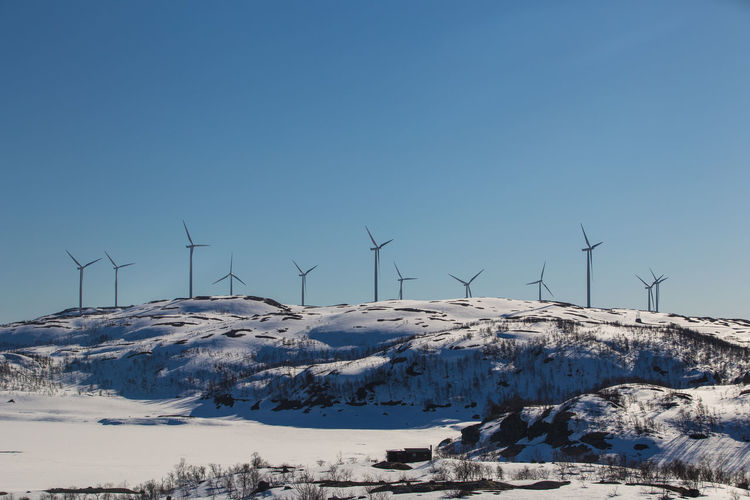 Wind Turbines on snowy hill Alternative Energy Beauty In Nature Blue Cold Temperature Day Environmental Conservation Field Fuel And Power Generation Industrial Windmill Landscape Nature No People Outdoors Renewable Energy Rural Scene Scenics Sky Snow Tranquil Scene Tranquility Wind Power Wind Turbine Windmill Winter