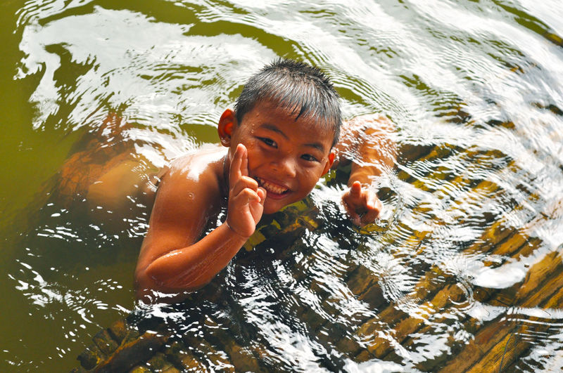 Portrait Of Smiling Boy Swimming In Lake