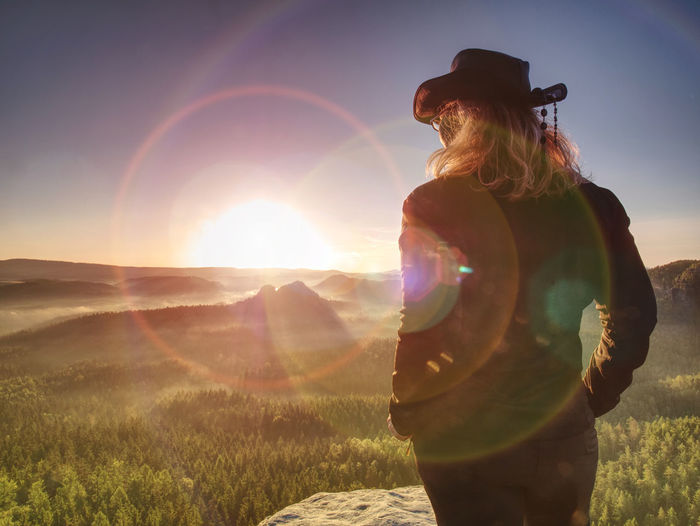 Cheering young woman traveler hiking on rocky mountain promontory above sharp tree tops.