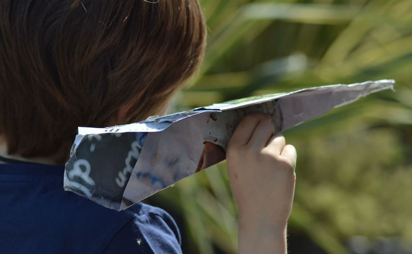 Rear view of boy holding paper airplane