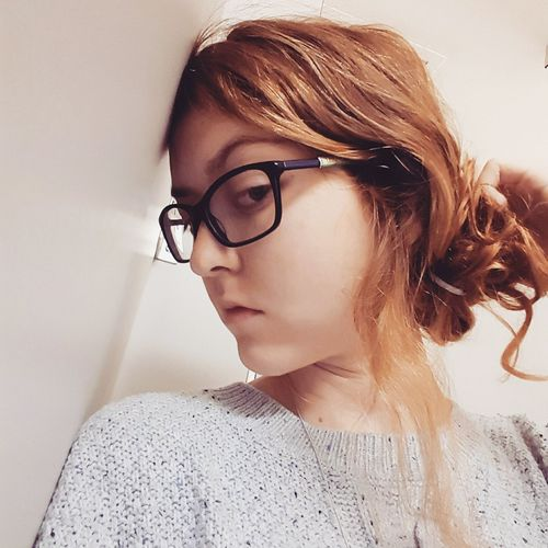 Portrait Of Young Woman Wearing Eyeglasses Against Wall