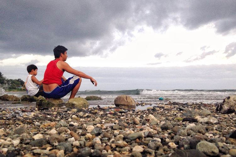 Two People Son And Father Bonding Time Horizon Over Water Rocky Beach Sitting Beauty In Nature Sea Real People Tranquil Scene Lifestyles Outdoors Togetherness Family❤ Family Matters Eyeem Philippines IMography Iphoneonly