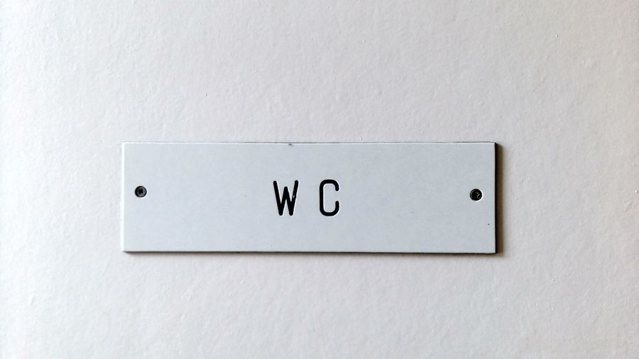 Close-up of restroom sign on wall