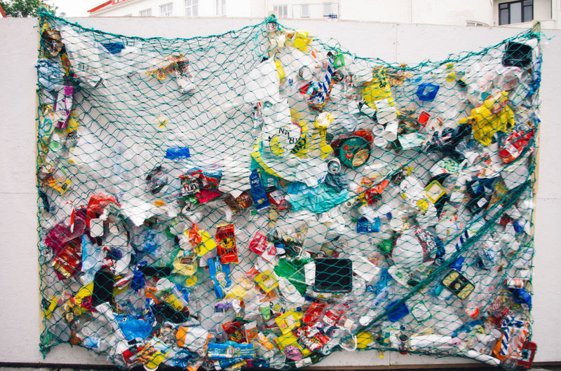 Multi colored garbage in net against wall