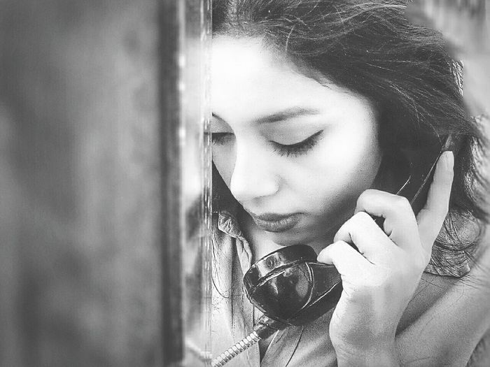 Close-up of woman holding telephone and looking down