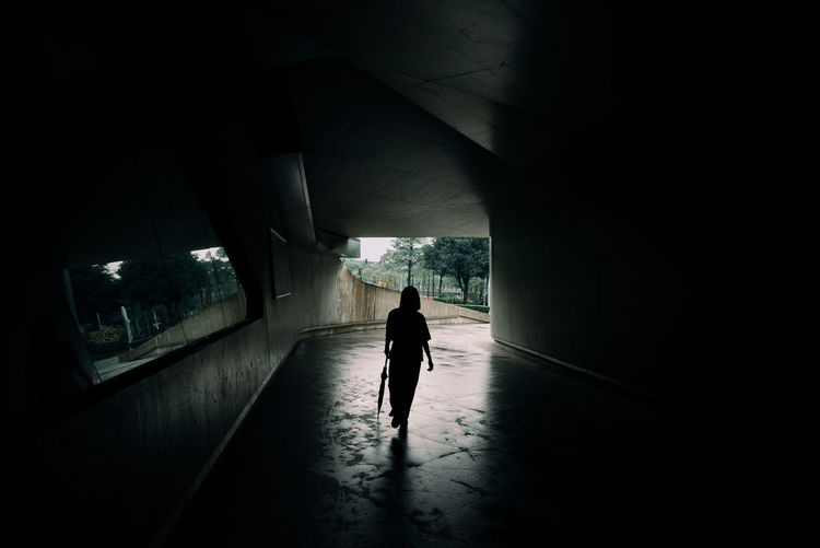 Rear view of woman walking under bridge