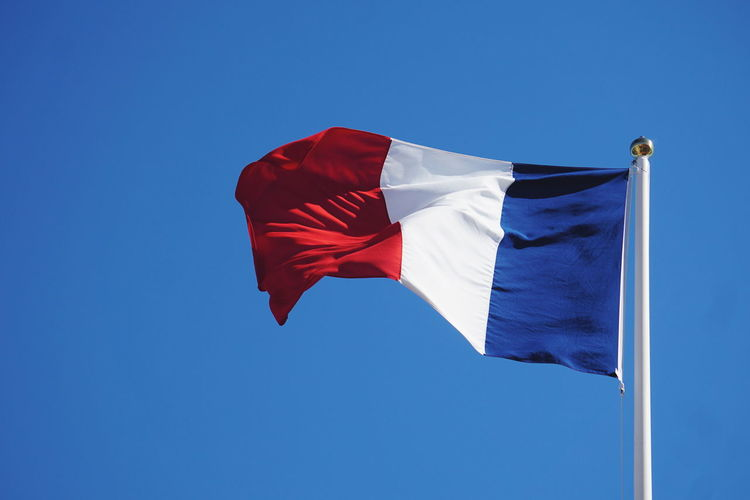Low Angle View Of French Flag Against Clear Blue Sky