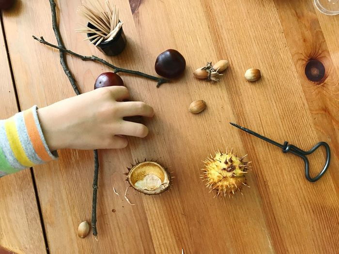 Cropped hand of person holding chestnut on wooden table