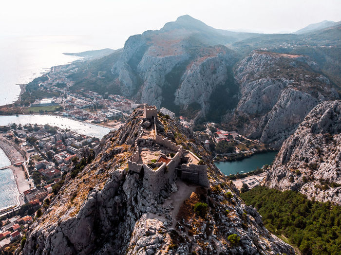 Aerial view of rock formation and pirate castle overlooking valley in omis, croatia.
