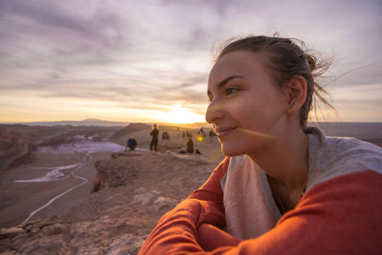 Side view of smiling young woman sitting on cliff against sky during sunset