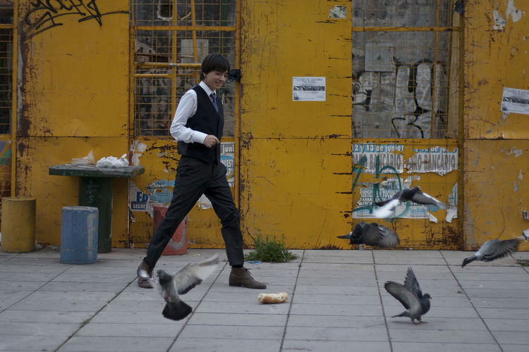 Full length of smiling man walking on footpath by pigeons